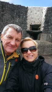 Louise and Michael visiting Ireland, standing in front of the ancient tomb at New Grange.